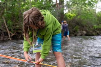 Peaks & Potentials camper studying stream flow. Photo by Brendan Kristiansen.